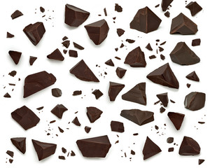 Broken, cracked or crushed dark chocolate parts from top view isolated on white background