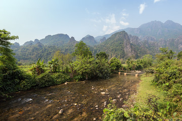Beautiful view of a tiny bamboo bridge over a shallow and idyllic river and striking karst limestone mountains near Vang Vieng, Vientiane Province, Laos, on a sunny day.