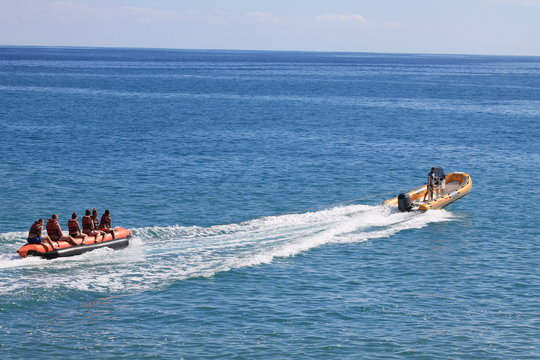 Banana boat ride being pulled by a speed boat on a beautiful sunny day.