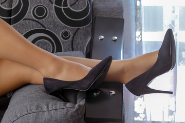 Beautiful women's legs with black shoes on the bed. Young woman lying on the bed with legs leaning against to the pillow.