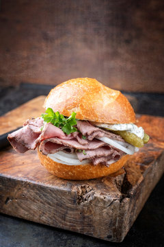 Traditional sliced cold cuts roast beef sandwich with onion, gherkin and remoulade offered as closeup on an old wooden board with copy space