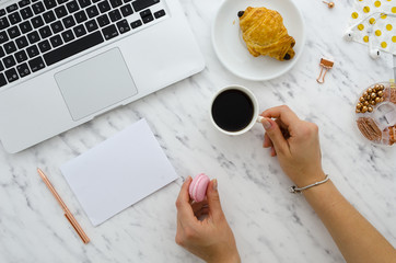 Blank paper mockup. Woman holding cup of coffee on marble background with laptop, croissant and office supplies flat lay top view hero header