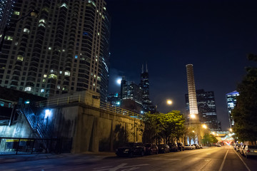 Fototapete - Chicago night street scene with a city tower, a smokestack, the