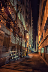 Fototapete - Dark and eerie downtown urban city alley with a fire escape next