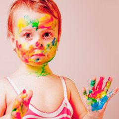 Humorous portrait of little cute child girl with children's makeup and painting colorful hands.