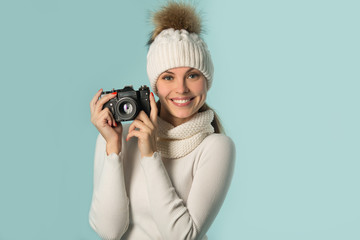 beautiful young girl in winter hat with a camera in hand on a blue background