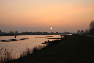 sunrise above the river Hollandsche IJssel at the village Nieuwerkerk in the Netherlands.