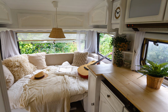 Inside the camper van. Unfilled bed, pillows, guitar, book, hat, white wooden decoration of the house on wheels.