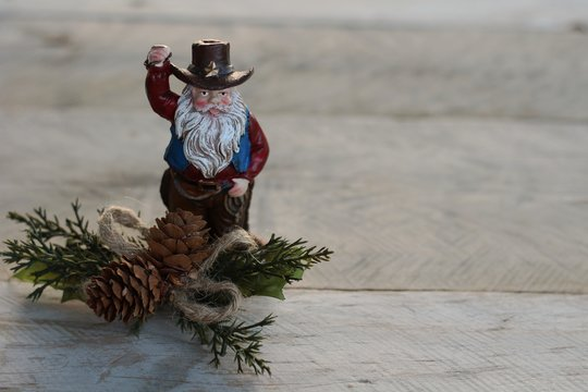 cowboy Santa Claus with beard standing next to pine cones and pine branches on a natural wood background with writing space