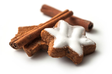 closeup of christmas biscuit shaped star with cinnamon stick on white background