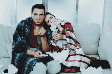 Sick Couple Sitting on Sofa in Checkered Blankets.