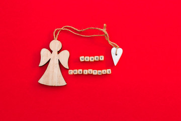 Christmas wooden angel with heart and twine with words Merry Christmas on little bricks on bright red background. Minimalism concept. Natural eco materials New Year toy.  Top view. Postcard template