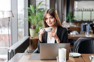 Young woman drinking coffee. Female holding cup. Sitting in coffee shop at wooden table. On table is gray aluminum laptop. Girl blogging, browsing internet, chatting