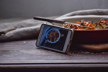 Instagram photography blogging workshop concept. phone near a stylish plate with grilled vegatables on wooden rustic background.