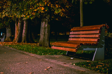 Late night shot of a bench lightened by a lamp in a public park. Sad autumn background