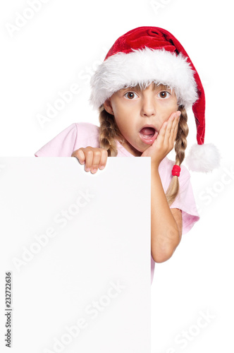 3be909f83ed Portrait of surprised little girl in Santa hat with white blank. Child  wearing Santa Claus