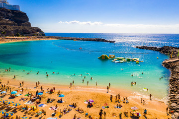 July 10, 2018. Amadores beach, Gran Canaria, Spain. People lying on the beach under the sun. Sunbeds, sun umbrellas and many people in the swimming suits.