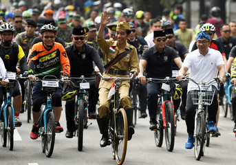 Indonesia's President Joko Widodo  waves to people as he rides a bicycle with West Java governor Ridwan Kamil in commemoration of Heroes' Day on a street in Bandung