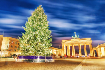 Lovely Christmas Advent night scenery of Brandenburg Gate with Christmas Tree in Berlin, the capital of Germany, Europe. Winter holidays background. Brandenburg Gate is iconic landmark.
