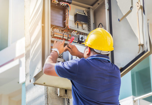 Electrician screwing equipment repairing in fuse circuit breaker box