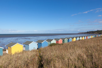 Row of colourful wooden beach huts.