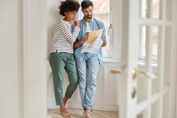 Photo of mixed race lady and male have inofficial meeting, compare prices of different providers, pose bare foot in empty room with documents, look through complete budget, dressed casually.