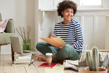 Positive freelancer with dark skin, toothy smile, checks current account on laptop computer, feels relaxed as works at home, sit in lotuse pose at floor, fills in documentation with pencil, uses books