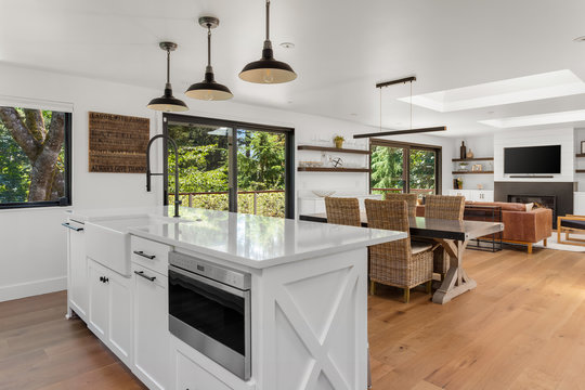 Kitchen in open concept-home with view of living and dining rooms. Interior is white and bright due to skylights.