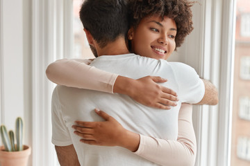 Positive dark skinned wife embraces her husband, happy to be close to lover, give warm hug to each other, stand near window background. Multiethnic relationship and love concept. Togetherness
