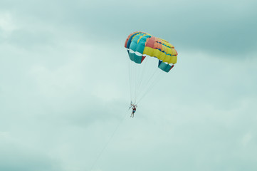 Skydiver flying with a colorful parachute on sky background