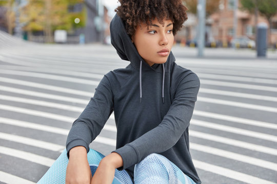 Horizontal shot of thoughtful swag African girl with pensive expression, dressed in hoodie and leggings, has rest on asphalt in sportsground, focused aside. Street lifestyle and youth concept