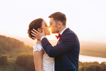 The groom kisses on the lips of a young bride in nature
