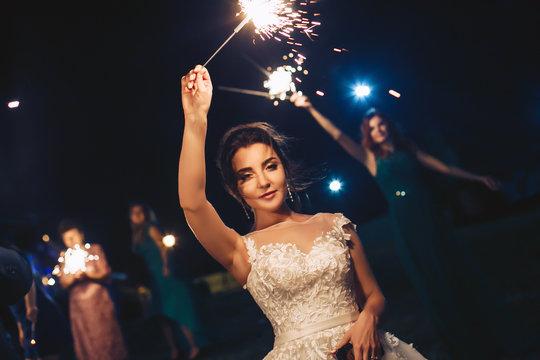Bride during the evening wedding ceremony waving sparkler