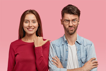 Wall Mural - Studio shot of cheerful brunette smiling woman points with thumb at her displeased male who keeps hands crossed, express different emotions, isolated over pink studio wall. Look at this guy!