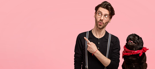 Shocked impressed guy has trendy haircut, bristle, wears round glasses, black shirt, stands near his favourite pet, indicates with index finger at copy space on right side, shows something incredible