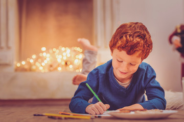 Dear Santa. Adorable ginger-haired pre-teen boy lying on the floor near the chimney, writing a letter to Santa Clause and drawing on it