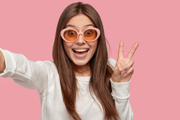 Glad dark haired Caucasian lady makes peace sign, wears fashionable shades, dressed in white clothes, smiles positively, holds unrecognizable device. Say hello to technology. Woman takes shot
