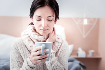 Feeling relaxed. Portrait of young peaceful woman holding a cup of tea while looking at it and expressing quietness