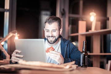 Being happy. Joyful male person expressing positivity and touching laptop while watching video
