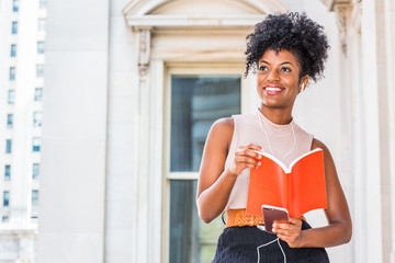 Young Happy African American female college student with afro hairstyle sitting by vintage style office building in New York, reading red book, listening music with earphone and cell phone, smiling..