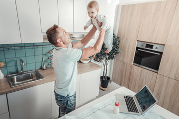 Reliable support. Satisfied strong pleasant father standing in the kitchen lifting a baby and smiling.