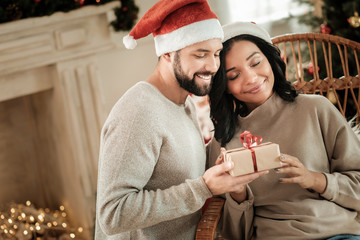 Christmas gifts. Nice happy young couple being together and looking at the gift while celebrating Christmas