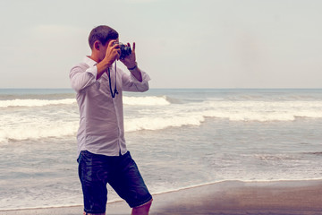 A man is taking pictures on the background of the sea