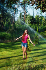 Beautiful girl with red long hair is refreshed in the park when watering the lawn