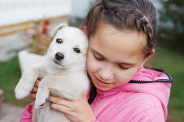 Girl with pigtails in a pink jacket hugs and kisses a white puppy.