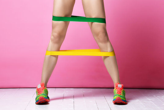 Fitness instructor woman legs exercising working out with green and yellow rubber resistance band on modern pink