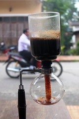 Street view in the town center of Luang Prabang of traditional Laos coffee percolating through heat into a pot with a motorcycle passing in the background.