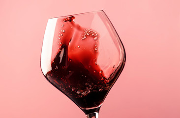Dry red wine, splash in glass, pink background, defocused in motion image, shallow depth of field