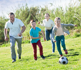 Mother and father with two kids  running after  ball