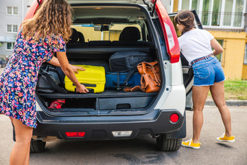 two woman packing luggage in car trunk